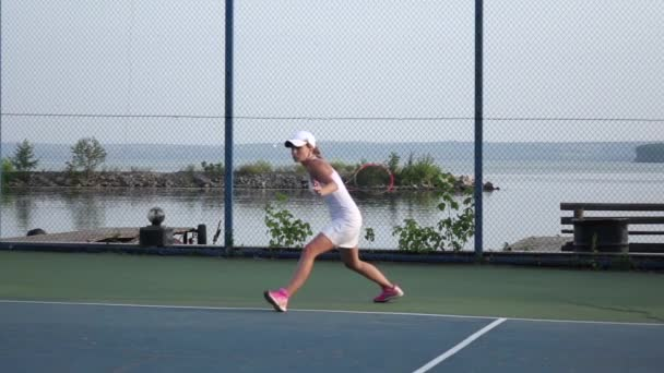 Women playing tennis. Player serving tennis ball with tennis racket. Slow motion