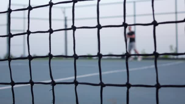 Men tennis player expecting the tennis ball on court, net in front. Dolly shot. Slow motion