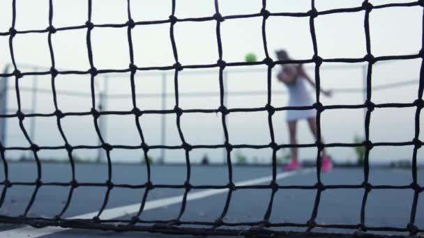 Tenisový míč. Tenisová síť. Zpomaleně