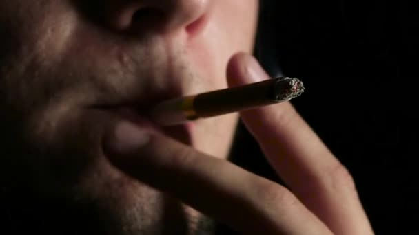 raucht eine Zigarette in einem dunklen Raum. schwarz. Nahaufnahme. Zeitlupe