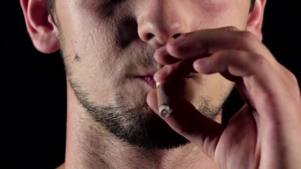 Man smokes a cigarette. He holds a cigarette between two fingers. Black. Close up. Slow motion