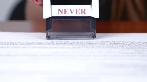 Lidé staví obdélníkové razítko na dokumentu. Detailní záběr
