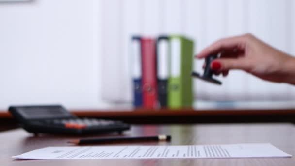 Zaměstnance umístí razítko na smlouvě. Detailní záběr