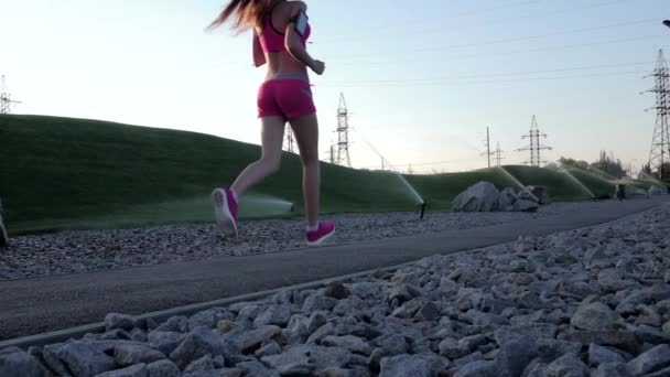 Runner woman running in park exercising outdoors. Slow motion