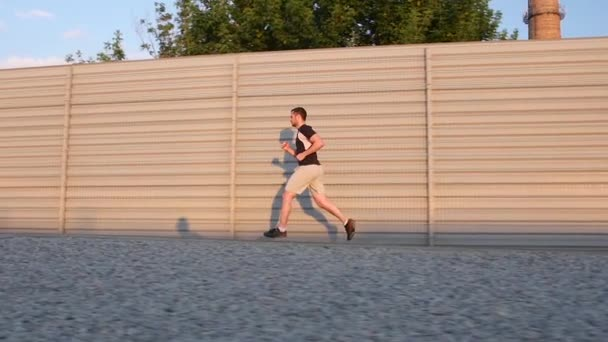Runner - athlete man running training outdoors exercising on mountain road. Slow motion
