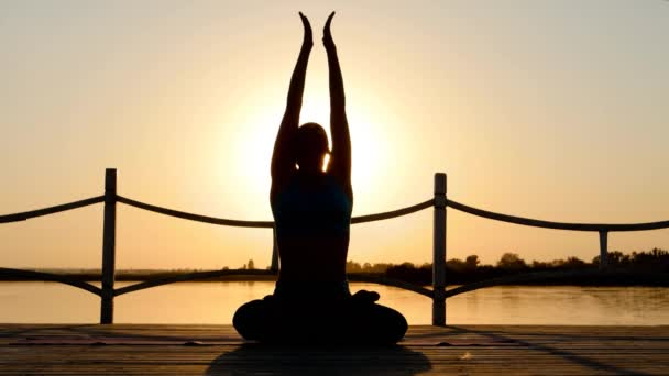 Junge Frau praktizieren Yoga in Sunflares am Strand bei Sonnenuntergang