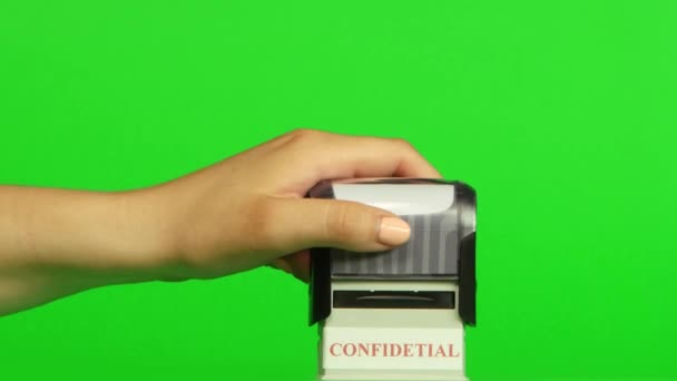 Razítko Confidetial na zeleném pozadí. Zblízka. Zelená obrazovka