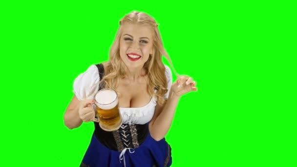 Bayerisches Mädchen in bayerischer Tracht reicht jemandem ein Bier und lächelt. Green Screen