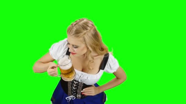 Frau in bayrischer Tracht trinkt ein Gläschen Bier. Green Screen
