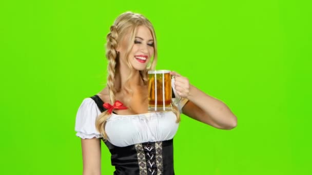Mädchen in bayerischer Tracht trinkt Bier und zeigt Daumen. Green Screen