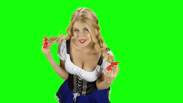 Mädchen in bayerischer Tracht flirtet mit jemandem. Oktoberfest. Green Screen
