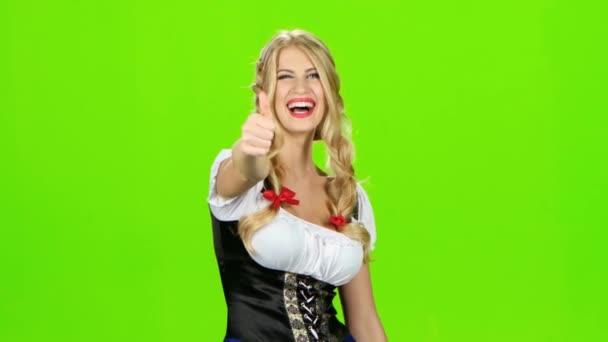 Frau in bayerischer Tracht lacht und zeigt Daumen. Green Screen