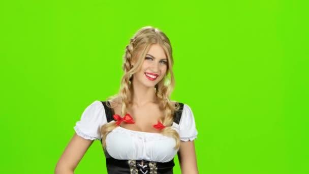 Frau in bayrischer Tracht lacht und Daumen nach oben zeigt. Green-screen