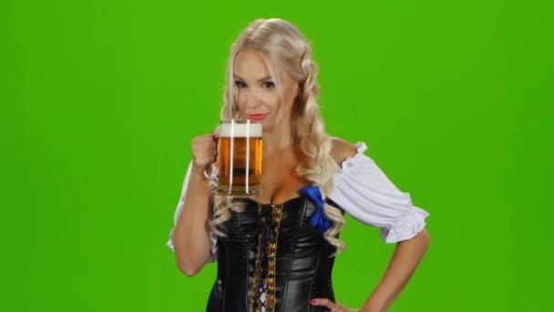 Frauen in traditioneller bayerischer Tracht trinken Bier und zeigen Daumen hoch. Green Screen