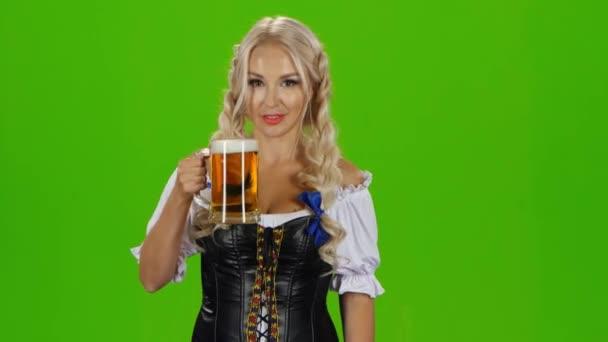 bayerisches Mädchen mit Bier, das Daumen hoch zeigt. Green Screen