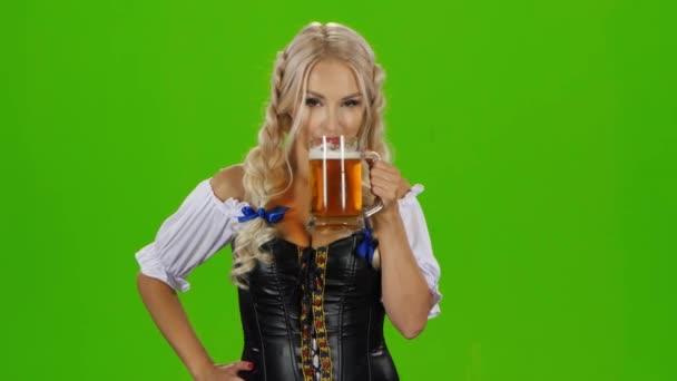 Bayerin trinkt ein Bierglas, zeigt Daumen hoch und zwinkert. Green Screen