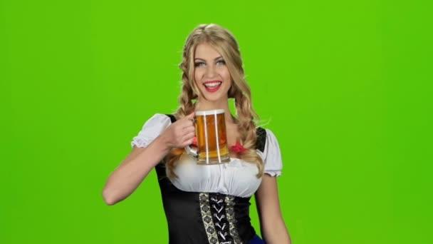 Dívka v bavorském kroji fouká na pivní pěnu. Zpomalený pohyb. Zelená obrazovka