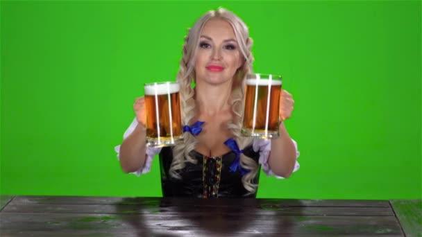 Bayerische Mädchen nimmt auf dem Tisch zwei Gläser Bier Nd zeigt Daumen. Green-Screen. Slow-motion