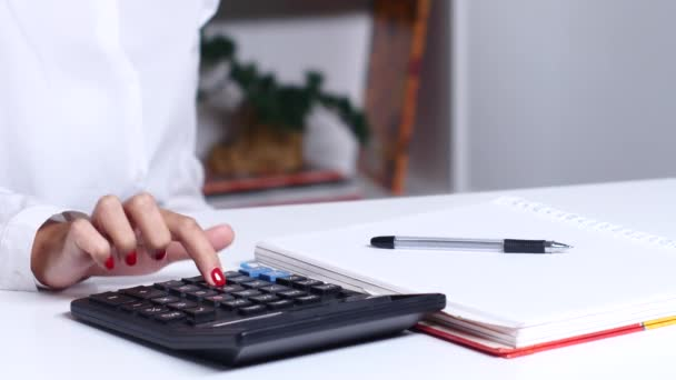 Woman counting on calculator