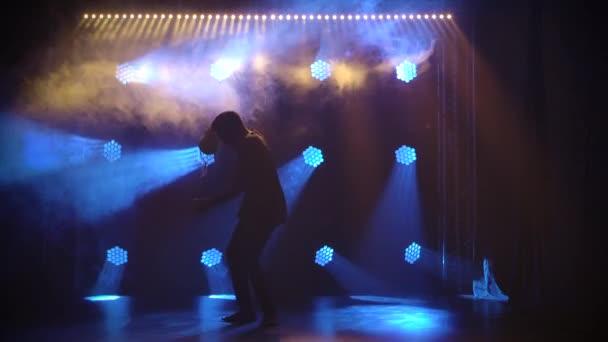 Silueta černocha, který tančí lidový tanec a hraje africký bicí buben shekere. Umělec samec vystupuje v tmavém studiu na pozadí modrých dynamických světel a kouře. Zpomalený pohyb