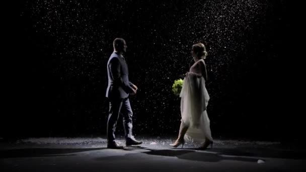 Šťastný pár zamilovaný přiblížit navzájem a políbit na pozadí padajícího sněhu. Muž v obleku a žena v bílých dlouhých šatech na černém pozadí v paprscích studiového světla. Zpomalený pohyb