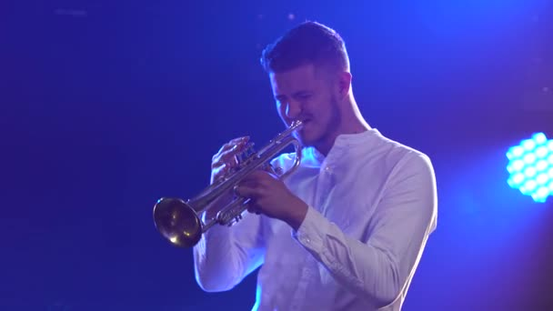 Solo concert of a male musician playing the trumpet. A talented man performs a melody of classical instrumental music in a dark studio with blue light. Side view. Close up.