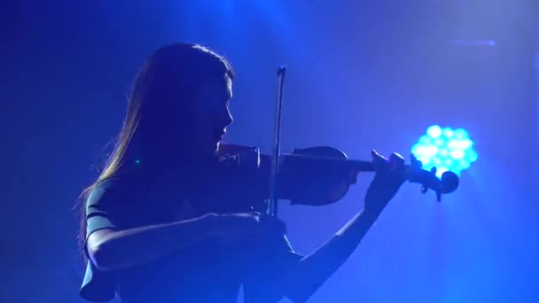Silhouettes of a charming professional violinist playing the violin. Rehearsal in a smoky studio with blue lights. Close up.