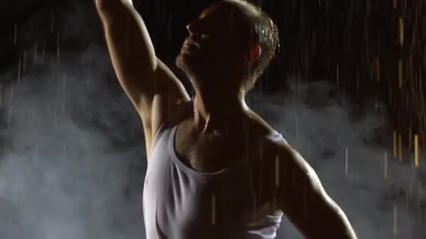 Male dancer dancing elements of salsa in the pouring rain in a dark smoky studio. A silhouette of a man in a wet white tank top enjoys the dance. Torso close up in slow motion.