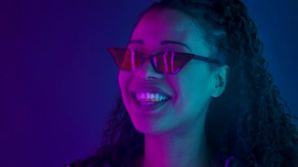 Portrét mladé krásné ženy Afroameričanky ve stylových slunečních brýlích s úsměvem, žvýkačkou a foukáním bubliny. Zblízka osvětlená tvář pestrobarevnými neonovými světly. Zpomalený pohyb.