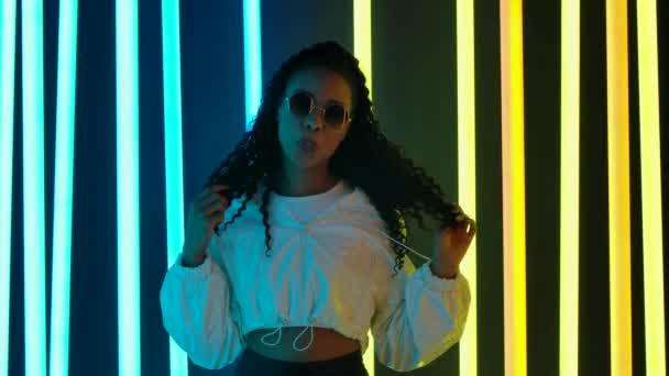 Portrét mladé krásné ženy Afroameričanky ve stylových slunečních brýlích žvýkající žvýkačku a foukající bublinu. Zpomalený pohyb.