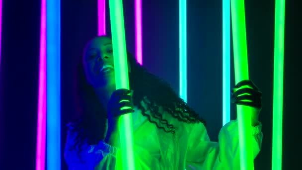 Portrét mladé krásné ženy Afroameričanky s dlouhými kudrnatými vlasy pózuje proti tmavému studiu s pestrobarevnými neonovými světly. Zpomal. Zavřít.