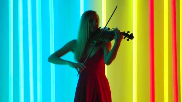 Představení talentovaného houslisty. Hezká žena v dlouhých červených šatech nacvičuje v tmavém studiu na pozadí jasných neonových světel. Zpomalený pohyb.