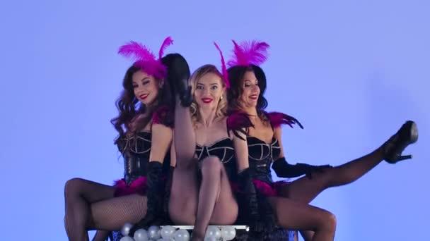 Wunderschöne sexy Burlesque-Tänzerinnen posieren verspielt neben einer großen schwarzen Torte. Heiße Weibchen tanzen auf blauem Studiohintergrund. Festliche theatralische Tanzshow. Aus nächster Nähe. Zeitlupe.