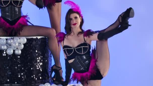 Szexi fiatal nők fekete testruhában, lila tollakkal a torta tetején. Három burleszk táncos pózol egy elszigetelt világoskék háttérrel a stúdióban. Közelről. Lassú mozgás..