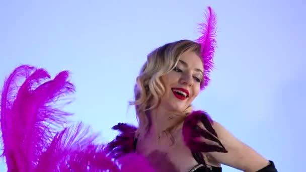Három szexi burleszk táncos pózol, miközben egy nagy fekete tortán ülnek pezsgős poharak mellett. Bájos nők, lila tollakkal a kezükben, kék stúdió háttérrel. Közelről. Lassú mozgás..