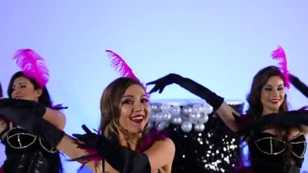 Gyönyörű szexi nők játékosan táncolnak egy nagy fekete torta mellett. Burleszk táncosok erotikus jelmezben, kék stúdió háttérrel pózolva. Ünnepi színházi tánc show. Közelről. Lassú mozgás..