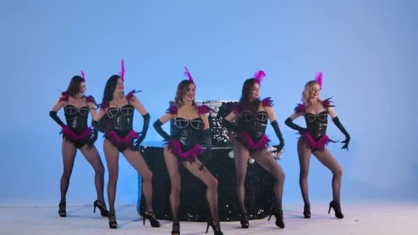 Imádnivaló kabaré táncosok szexi jelmezben táncolnak együtt egy nagy fekete tortával. Szenvedélyes nők pózolnak világoskék háttérrel a stúdióban. Lassú mozgás..