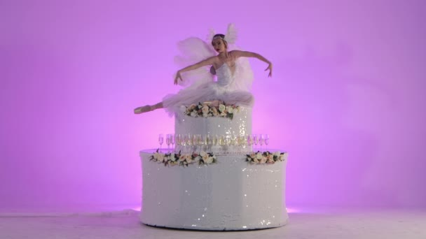 Egy fehér hattyúnak öltözött finom női balerina pózol egy virágokkal díszített torta tetején. A szőke kecsesen mozog lassított felvételen rózsaszín háttérrel a stúdióban. Ünnepi színházi
