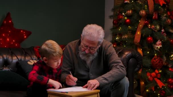 Großvater bringt seinem Enkel das Zeichnen mit Filzstiften bei. Ein eleganter grauhaariger Mann mit einem kleinen Jungen sitzt auf einem Sofa in einem geschmückten Raum neben einem leuchtenden Weihnachtsbaum. Aus nächster Nähe. Zeitlupe.