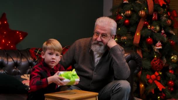 Der kleine Junge im festlich rot karierten Hemd schüttelt in Erwartung einer Überraschung die Geschenkbox. Großvater und Enkel sitzen auf dem Sofa in einem geschmückten Raum neben dem leuchtenden Weihnachtsbaum. Aus nächster Nähe. Zeitlupe.