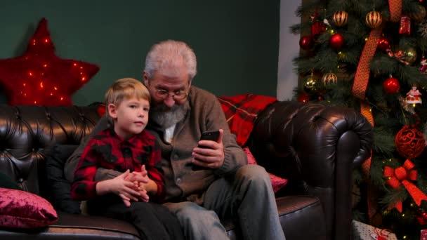 Eleganter alter Mann und kleiner Junge surfen auf einem Smartphone und haben Spaß. Großvater und Enkel sitzen auf einem Sofa in einem geschmückten Raum neben einem leuchtenden Weihnachtsbaum. Aus nächster Nähe. Zeitlupe.