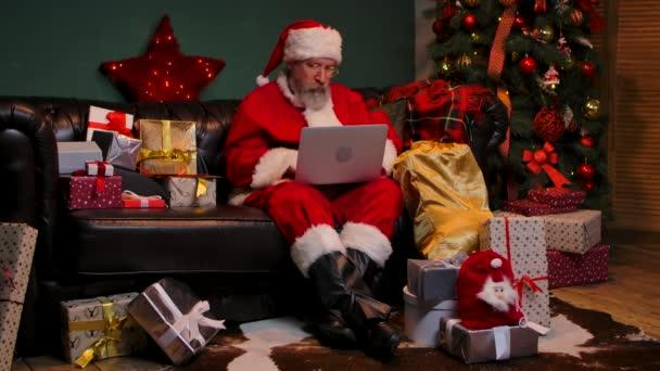 Der Weihnachtsmann bestellt per Laptop Geschenke im Internet. Ein alter Mann mit Bart, rotem Anzug und Hut sitzt auf einem Sofa in einem geschmückten Raum neben einem leuchtenden Weihnachtsbaum. Zeitlupe.