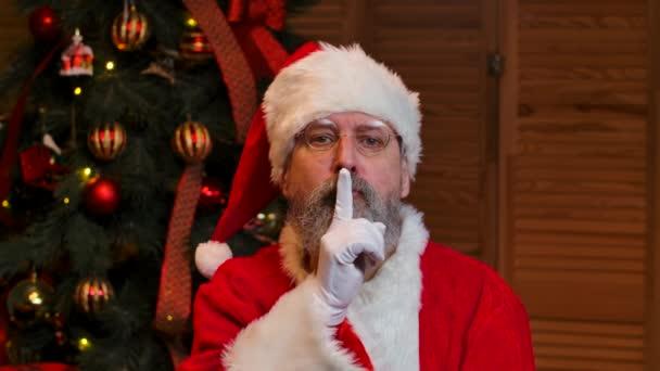 Portré Mikulás keres nyugdíjas körül, teszi a titkos gesztus és kacsint. Vénember piros öltönyben és kalapban a karácsonyfa hátterében játékokkal és fényekkel. Közelről. Lassú mozgás..