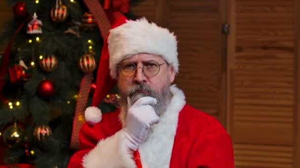Portré Mikulás nézi kamera figyelmesen hallgat, és tesz egy gesztus rendben. Öreg ember piros öltöny és kalap hátterében karácsonyfa játékok és fények. Közelről. Lassú mozgás..