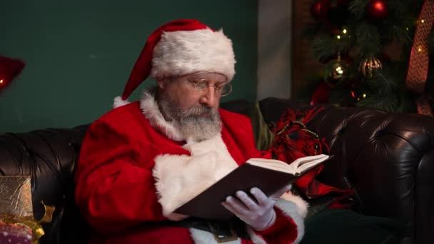 Santa Claus čte knihu s pohádkami. Starý muž s plnovousem v červeném obleku a kloboukem sedí na pohovce ve zdobeném pokoji poblíž zářícího vánočního stromku a krabic s dárky. Zavřít. Zpomalený pohyb.