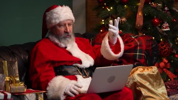 Aranyos Mikulás kommunikál videóhívás segítségével laptop. Az öreg szakállas vörös öltönyben és kalapban ül a kanapén egy díszített szobában, közel a ragyogó karácsonyfához. Közelről. Lassú mozgás..
