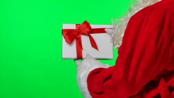 Kilátás a Mikulás mögül fehér kesztyűs szakállal és piros ruhával megpörget egy ajándékdobozt a kezében. Elszigetelve egy zöld vásznon egy stúdióban. Krómkulcs. Közelről. Lassú mozgás..