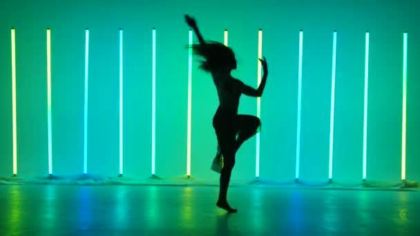 Eine barfüßige Schauspielerin tritt vor der Kulisse bunter Neonröhren auf. Eine Ballerina tanzt plastisch Pirouetten und dreht sich in Zeitlupe. Silhouette.