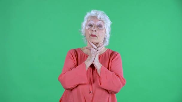 Portrait einer älteren Frau, die in die Kamera lächelt und mit jemandem spricht. Grauhaarige Großmutter in roter Bluse auf grünem Bildschirm im Studio. Nahaufnahme.