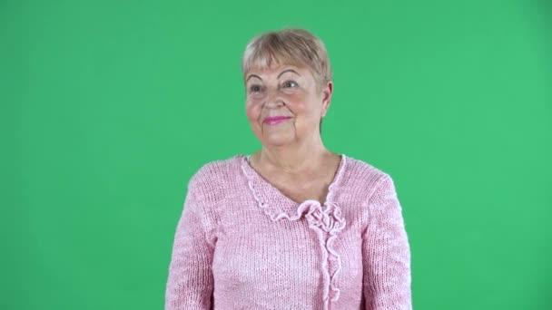 Portré idős nő néz a kamerába és mosolyog. Ősz hajú nagymama, rövid hajjal, rózsaszín pulóverben, zöld vásznon a stúdióban. Közelről..